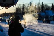 A man smokes a cigarette outside of Moocher's Bar in Nenana, Alaska