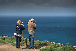 Tourists enjoy the spectacular views as they stand on the cliffs at Carnewas at Bedruthan in Cornwall.