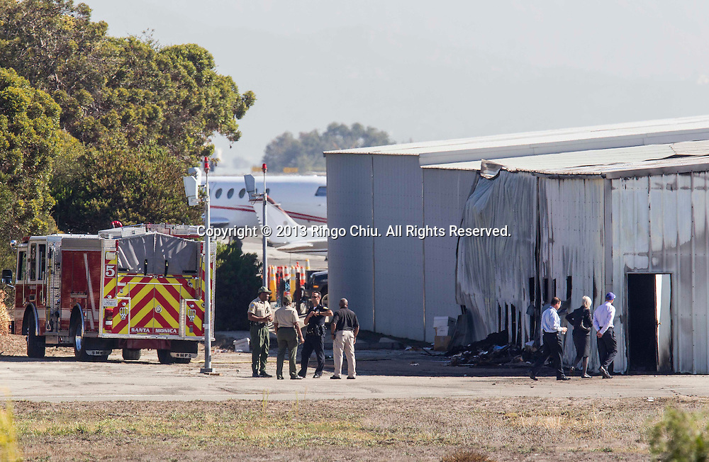 Airport officials and investigators stand near a collapsed hangar at the site of a plane crash in Santa Monica, California on Monday, September 30, 2013. A twin-engine Cessna Citation jet flying in fromIdaho crashed into a hangar after landing at Santa Monica Airport  and veering off the runway, causing the structure to collapse, sparking an explosive fire and killing all aboard around 6:20PM, Sunday. (Photo by Ringo Chiu/PHOTOFORMULA.com)