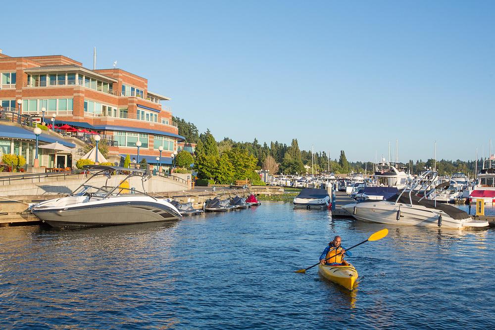 United States, Washington, Kirkland, man kayaking near Carilon Point Marina.  MR