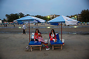 Two Asian women relax on sun-loungers on Laboni Beach in Cox Bazar, Chittagong Division, Bangladesh, Asia.