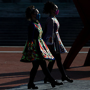 Sanibel Kujawa (cq), 14, left, and Ellie Landis (cq), 16, both of Toledo and part of Molly's Irish Dancers, perform in celebration of St. Patrick's Day outside the Toledo Museum of Art in Toledo on Wednesday, March 17, 2021. THE BLADE/KURT STEISS