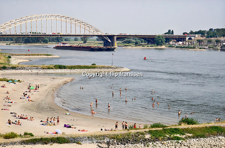 Nederland, nijmegen, 25-7-2019Mensen trekken massaal naar de oevers van de waal en de spiegelwaal in het rivierpark aan de overkant van Nijmegen . De recordwarmte drijft mensen naar het water . Om niet helemaal te verbranden liggen veel badgasten in de schaduw van de spoorbrug . Het is verboden in de rivier te zwemmen vanwege de stroming het het drukken scheepvaartverkeer . Warmste, heetste dag sinds de weermetingen. Hitterecord,weerrecord,warmterecord . klimaatverandering, opwarming,klimaat, aarde .Foto: Flip Franssen