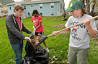 LHS National Honor Society students Jared Guilmett, Priya Nathala and McKenna Caldwell rake and bag leaves while Emily Dionne and Abby Teichart wash windows during the groups annual Spring clean up project Thursday.  (Karen Bobotas/for the Laconia Daily Sun)