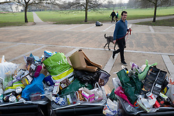 © Licensed to London News Pictures. 31/03/2021. London, UK. A man walks his dogs past overflowing bins in Greenwich Park after hundreds of people visited the park to enjoy sunny weather and take advantage of new lockdown rules that allow groups of six to meet outside. Photo credit: George Cracknell Wright/LNP