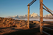A rustic ranch gate frames the Teton range on a cold autumn morning in Grand Teton National Park, Wyoming.