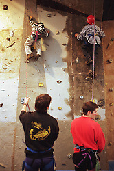 Teenagers using climbing wall with assistance of supervisors,