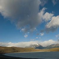 Clouds hover over Laguna Amarga, near Torres del Paine National Park, Chile. Mount Almirante Nieto dominates the background.