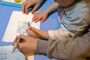 A prisoner plays with his child during a family visit. HMP Wandsworth, London, United Kingdom