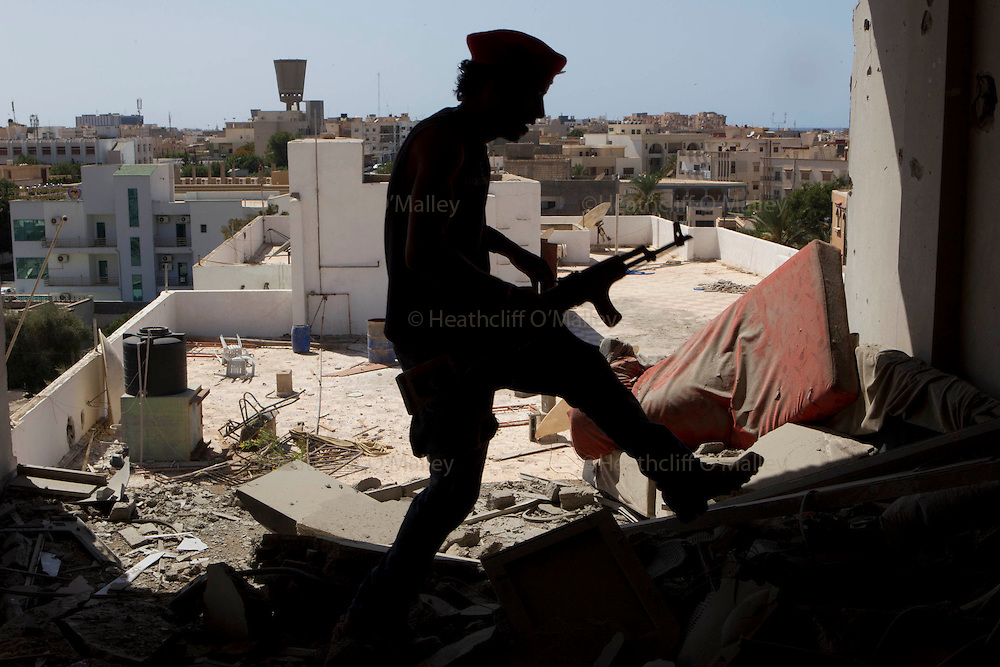 Sco0033837 .  Daily Telegraph..A neighbourhood guard inspects damage done to a residential home during the battle for the Bab al Azizia compound. The vast majority of the city is now in the full control of the rebels...Tripoli 29 August 2011. ............Not Getty.Not Reuters.Not AP.Not Reuters.Not PA