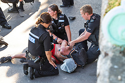 © Licensed to London News Pictures. 25/06/2020. Brighton, UK. Police break up a fight and arrests 2 young men. The arrest triggered a large scale police presence on the Brighton promenade.  One of the arrested men is made to wear a spit hood known to stop people spitting at police officers. Photo credit: Hugo Michiels/LNP