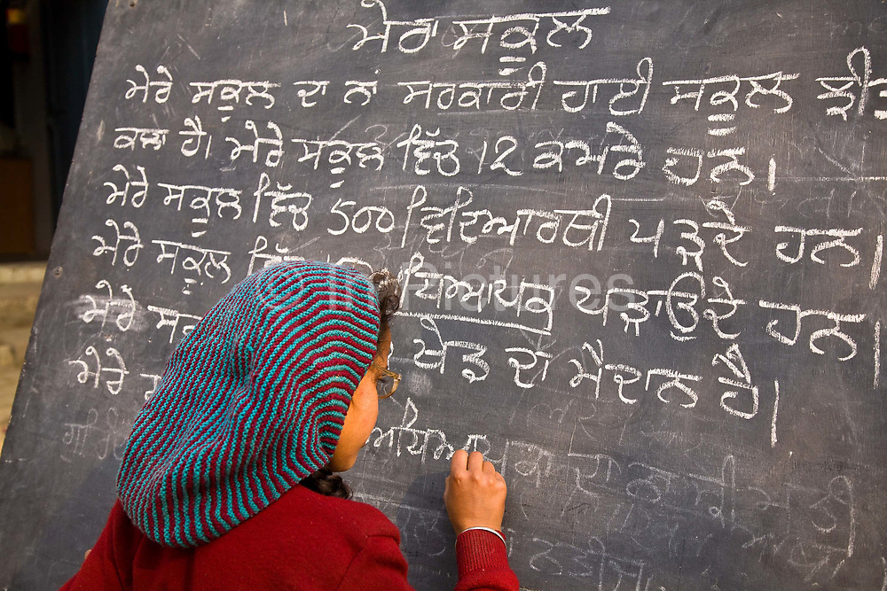 In a Punjabi rural school, a young girl  writes on school blackboard whilst other children look on in an open  courtyard, India.