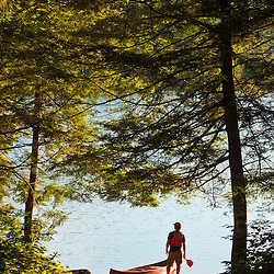 A man next to his canoe at Zack Woods Pond, Hyde Park, Vermont.  Early morning. Green River Reservoir State Park
