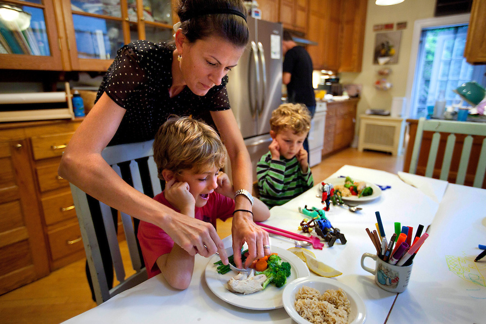 Leslie Astor cuts the food of son Jake Astor, 8, as his brother Michael Astor, 2, waits his turn inside their home in Brooklyn, N.Y., Sept. 16, 2011.