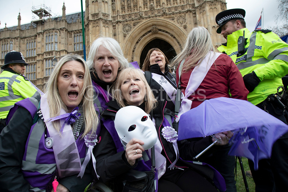 WASPI women protest joins in the Anti Brexit demonstration after breaking through the barriers onto College Green in Westminster on the day after the 'meaningful vote' when MPs again rejected the Prime Minister's Brexit Withdrawal Agreement and before a vote on removing the possibility of a No Deal Brexit on 13th March 2019 in London, England, United Kingdom. Women Against State Pension Inequality is a voluntary UK-based organisation founded in 2015 that campaigns against the way in which the state pension age for men and women was equalised. They call for the millions of women affected by the change to receive compensation.