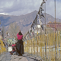 Tibetan Buddhist pilgrims prostrate themselves on a suspension bridge near the Potala, former home of the Dalai Lama. reflects in a pool in Lhasa, Tibet, China.  This was taken in 1986 and the view is now crowded with modern buildings.