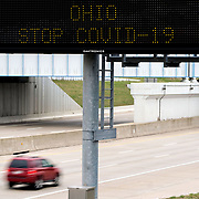 A motorist drives by as an ODOT dynamic message sign shows a message encouraging people to stay home amid the COVID-19 pandemic on I-280 in Oregon, Ohio, on Tuesday, March 31, 2020. THE BLADE/KURT STEISS