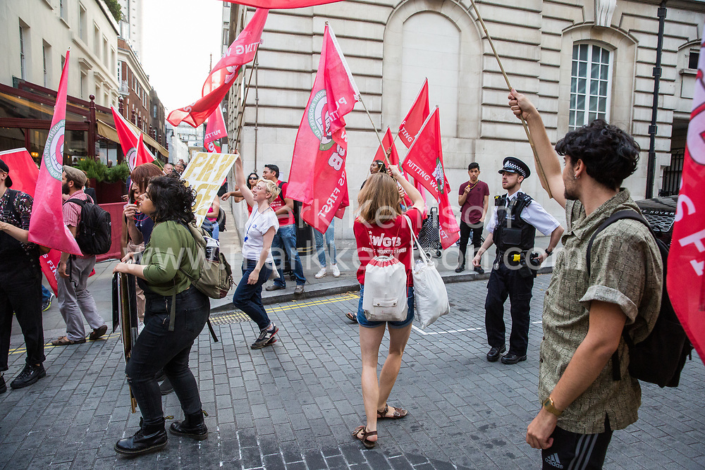 London, UK. 12 July, 2019. Members of the Cleaners and Facilities Branch of the IWGB (Independent Workers of Great Britain) trade union protest outside 5 Hertford Street in Mayfair, which also houses exclusive private club Loulou's, to call for its kitchen porters, recently outsourced through ACT Clean, to be paid the London Living Wage and given terms and conditions including suitable sick pay, holidays and pension contributions. Numerous unmarked security guards were present outside the venue.