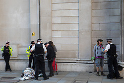 London, UK. 27th August, 2021. Police officers talk to environmental activists from Extinction Rebellion outside the Bank of England following a Blood Money March through the City of London on the fifth day of Impossible Rebellion protests. Extinction Rebellion were intending to highlight financial institutions funding fossil fuel projects, especially in the Global South, as well as law firms and institutions which facilitate them, whilst calling on the UK government to cease all new fossil fuel investment with immediate effect.