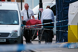 © Licensed to London News Pictures. 04/08/2016. London, UK. A private ambulance crew remove a body of a victim whilst forensic police officers investigating a mass stabbing incident, which left one woman dead and up to six people injured outside the Imperial Hotel in Russell Square, London. Photo credit: Tolga Akmen/LNP