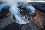 A lava lake within a collapse pit glows brightly inside of Pu'u 'O'o crater. Surrounded by fragile shelly pahoehoe, the pit can only be seen by air, as hazardous conditions around Pu'u 'O'o make it impossible by foot. Air charter courtesy of Paradise Helicopters.