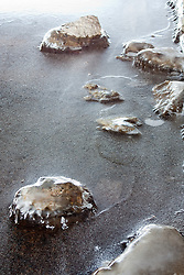 Rocks have a sheen of ice covering them after severa days of warm weather and a gradual re-freeze