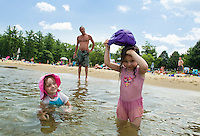 "Lily Lafond watches Layleah Wells pour her cap full of water over her head to cool off with ""Papa"" Jeff Wells at Weirs Beach on Wednesday afternoon.  (Karen Bobotas/for the Laconia Daily Sun)"