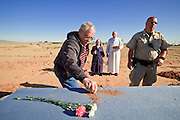 "18 MARCH 2010 - SURPRISE, AZ: Tom Lanphear (CQ) LEFT from Phoenix, places flowers and dirt in the shape of a cross on the caskets during burials in White Tanks Cemetery on Camelback Rd. in an unincorporated part of the county near Surprise. County Detention Officer Halucha (CQ) watches the inmates while Sister Mary Ruth Dittman (CQ) and Deacon Charles Shaw (CQ) officiate. The county spent about $2.5 million to inter indigent people in what is Maricopa County's ""potters field."" About 3,000 people, children and adults, are buried in the dusty field west of Phoenix.   PHOTO BY JACK KURTZ"