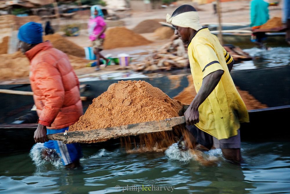 Sand divers transport sand from their boats to the banks of the Niger River at Segou, Mali. People dive to the bottom of the river, filling buckets with sand to be used in construction all over the country. Many people die each year doing this dangerous job
