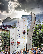 Surprisingly young children climb and rappel (abseil) while harnessed and roped on a practice wall in downtown Cortina d'Ampezzo, Italy, Europe. Afternoon sun rays burst through clouds over the Ampezzo Dolomites. The mountain town of Cortina d'Ampezzo (Ladin: Anpëz, German: Hayden, at 1224 meters/4016 feet elevation) is surrounded by the Dolomites (Dolomiti, a part of the Southern Limestone Alps) at the top of Valle del Boite in the Province of Belluno, Veneto region, Italy. This ski resort hosted the 1956 Winter Olympics. UNESCO honored the Dolomites as a natural World Heritage Site in 2009. This panorama was stitched from 3 overlapping photos.