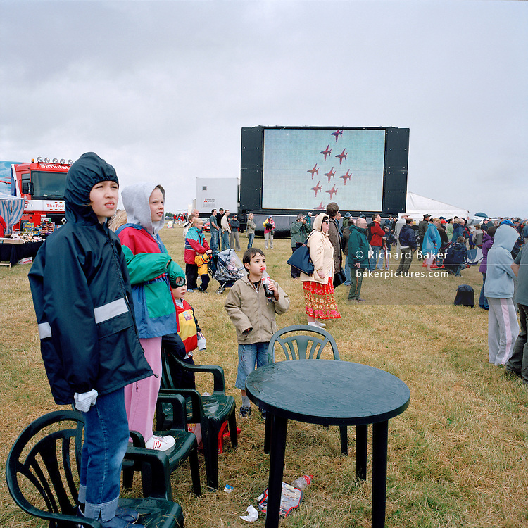 Young spectators watch display by the 'Red Arrows', Britain's Royal Air Force aerobatic team at RAF Kemble.
