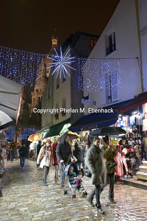 Visitors walk past restaurants and shops in the Montmartre neighborhood in Paris, France, Wednesday, Dec. 24, 2014. (Photo by Phelan M. Ebenhack)