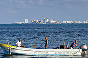 09 SEPTEMBER 2003 - CANCUN, QUINTANA ROO, MEXICO: Santo Ariel Loria Pacheco, RIGHT, brings his open fishing boat into Cancun, Quintana Roo, Mexico, after a day of fishing, Sept 9, 2003. Pacheco's father is a retired fisherman who also worked in the tourist industry before he was forced to retire for health reasons. The sons still fish from open boats in the waters off Cancun while their mother prepares take out meals for neighbors in their home. The family has lived in the region for years, since before Cancun was Cancun and was a small fishing community called Puerto Juarez. The high rise hotels of Cancun are in the background. PHOTO BY JACK KURTZ  economy  labour  food    poverty  culture