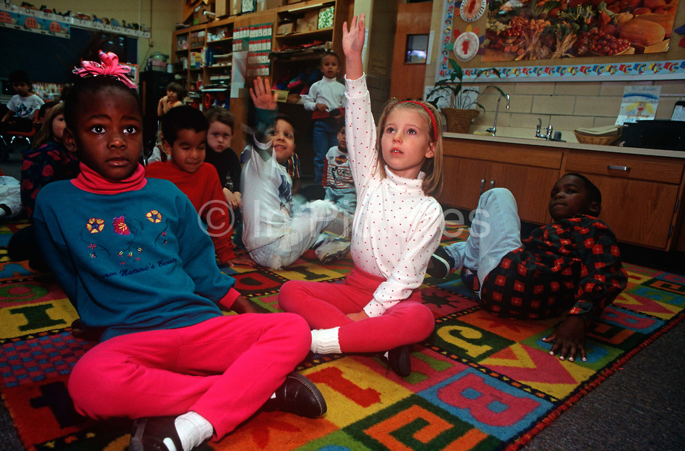 A confident 1990s child raises her hand while classmates sit on a classroom rug at the Ashford Park Elementary School, on 5th November 1995, in Atlanta, Georgia USA.