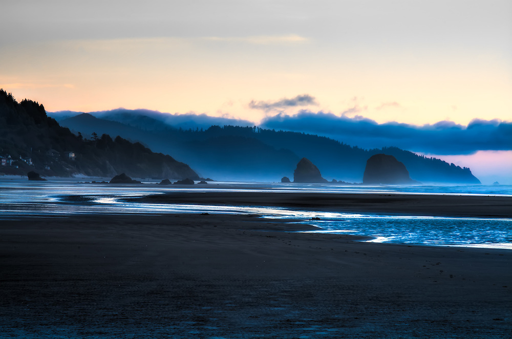 Dusk settles and sea mist rises among the cliffs and seastacks at Tolovana Beach on the Oregon Coast.