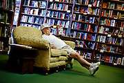 """SHOT 8/12/09 2:05:53 PM - Catching a quick nap on a couch at the the Tattered Cover Book Store on Colfax Avenue in Denver, Co. Colfax Avenue is the main street that runs east and west through the Denver-Aurora metropolitan area in Colorado. As U.S. Highway 40, it was one of two principal highways serving Denver before the Interstate Highway System was constructed. In the local street system, it lies 15 blocks north of the zero point (Ellsworth Avenue, one block south of 1st Avenue). For that reason it would normally be known as """"15th Avenue"""" but the street was named for the 19th-century politician Schuyler Colfax. On the east it passes through the city of Aurora, then Denver, and on the west, through Lakewood and the southern part of Golden. Colloquially, the arterial is referred to simply as """"Colfax"""", a name that has become associated with prostitution, crime, and a dense concentration of liquor stores and inexpensive bars. Playboy magazine once called Colfax """"the longest, wickedest street in America."""" However, such activities are actually isolated to short stretches of the 26-mile (42 km) length of the street. Periodically, Colfax undergoes redevelopment by the municipalities along its course that bring in new housing, trendy businesses and restaurants. Some say that these new developments detract from the character of Colfax, while others worry that they cause gentrification and bring increased traffic to the area. (Photo by Marc Piscotty / © 2009)"""