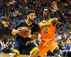 Feb 10, 2018; Morgantown, WV, USA; West Virginia Mountaineers forward Esa Ahmad (23) drives down the lane while guarded by Oklahoma State Cowboys forward Cameron McGriff (12) during the second half at WVU Coliseum. Mandatory Credit: Ben Queen-USA TODAY Sports