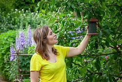 Putting up a bird feeder filled with sunflower seeds