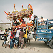 Pilgrims loading the cart onto a lorry to bring it back to Karachi. Some of the Hindu pilgrims walk for about 8 days in the blistering heat, from Karachi to the pilgrimage site (about 270 Km). They push a cart loaded with the deity from their local temple, bringing it to Nandi Mandir, the pilgrimage's main holy site. It is believed that accessing the pilgrimage on foot is more auspicious. The cart is loaded with a generator, playing loud Hindu music, and lights up at night. Pilgrims sleep out in the open or in small roadside hotels.
