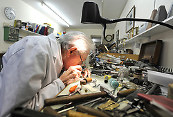 "©London News pictures...28/10/2010.  Dudley Taylor, 76, a clockmaker all his life working at his desk. Staff at Horological Workshops start the task of changing the 100's of clocks at their store in Guildford, Surrey, UK. Micahel Tooke who has owned the store for 43 years and worked in the clock business all his life said. ""at this time of year we get alot of people who bring clocks in for repair after they have changed the time incorreectly by winding back the hands manually"""