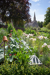 View over the vegetable and cut flower garden towards the house and church. Lilium regale in the foreground