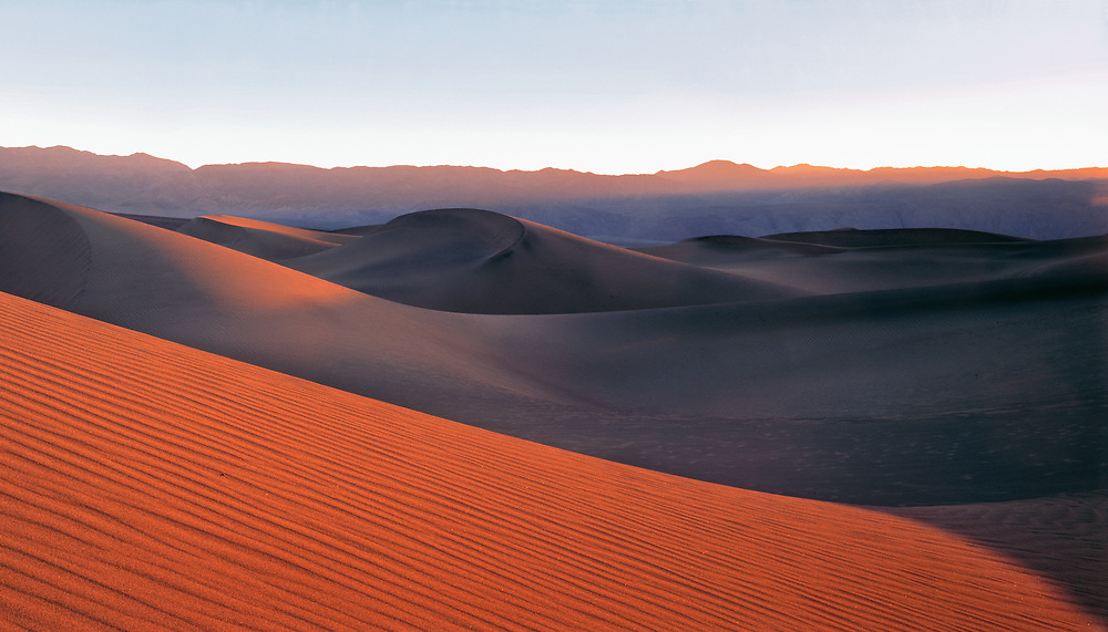 Evening light forms long shadows on this sand dune in Death Valley National Park, California.