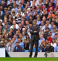 Photo. Jed Wee<br />Manchester City v Arsenal, FA Barclaycard Premiership, City of Manchester Stadium, Manchester. 31/08/2003.<br />Arsenal manager Arsene Wenger looks annoyed at his team's seeming inability to take advantage of Manchester United's loss to Southampton.
