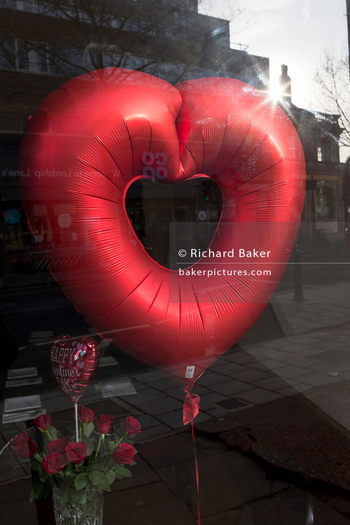 A red balloon is in the window of a local restaurant offering Valentine's Day meals on Lordship Lane in East Dulwich, on 13th February 2019, in London, England.