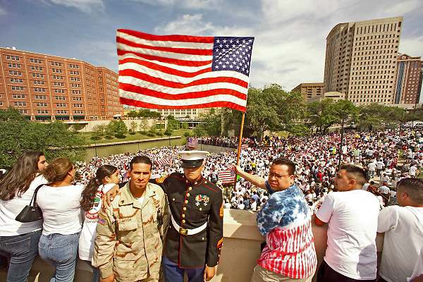 Stock photo of US Marines Staff Sgt. Jose Soto and US Army Staff Sgt. Shannon Arteche overlooking the thousands of protesters at Allen's Landing to fight for the rights of immigrants.