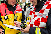 London Fire Brigade Sector Commander and Team Leader document the emergency details on their log sheet on Church Street, Stoke Newington, London, United Kingdom.  Their teams have just responded to an explosion in a shop basement.