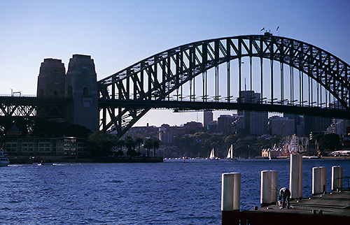 A fisherman prepares his line on a dock opposite the bridge on Sydney Harbour.