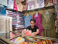 Boy reading about the prophet Mohammed in garment stall in a souq in the Fez medina, Morocco
