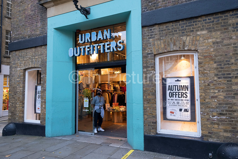Shop worker in the doorway of Urban Outfitters wearing a face mask as Londoners await the imminent second coronavirus lockdown it's business as usual in the West End with large numbers of people, some wearing face masks and some not, on what will be the last weekend before a month-long total lockdown in the UK on 1st November 2020 in London, United Kingdom. The three tier system in the UK has not worked sufficiently, to suppress the virus, and there have have been calls by politicians for a 'circuit breaker' complete lockdown to be announced to help the growing spread of the Covid-19.