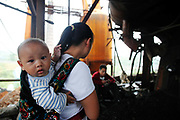 A mother carrying her young baby visit workers who are carrying out maintenance work on equipment at the Yuanhua Smelter in Daoxian County, Hunan Province, China, on 03 June, 2010. The company makes manganese alloys and additives that are widely used in the steel industry.